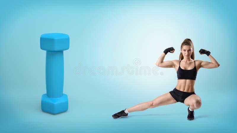 Een jonge geschikte vrouw in geschiktheid het sluiten zit in een lage kant uitvalt dichtbij een reuze blauwe domoor stock afbeeldingen