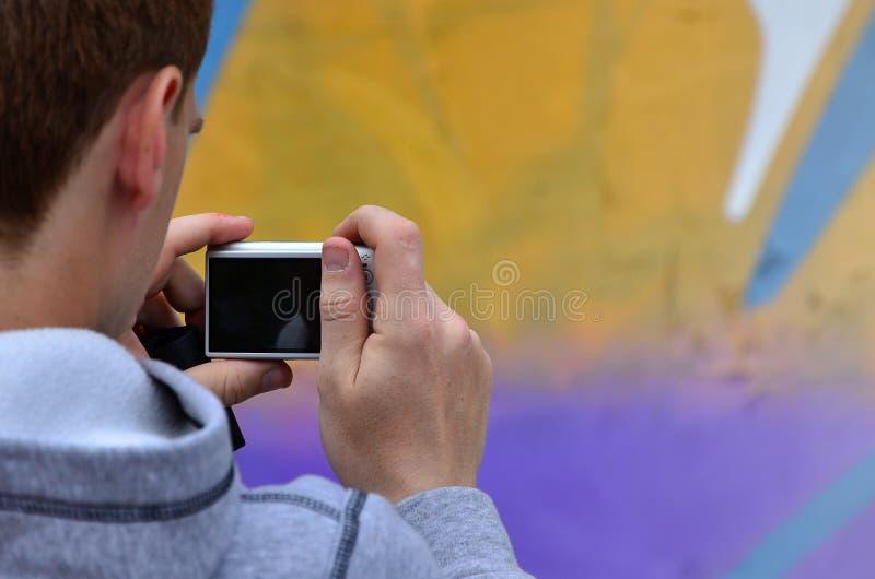 Een jonge graffitikunstenaar fotografeert zijn voltooid beeld op de muur stock fotografie