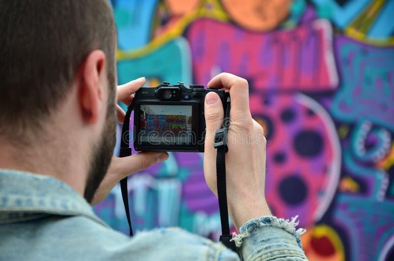 Een jonge graffitikunstenaar fotografeert zijn voltooid beeld op de muur royalty-vrije stock fotografie