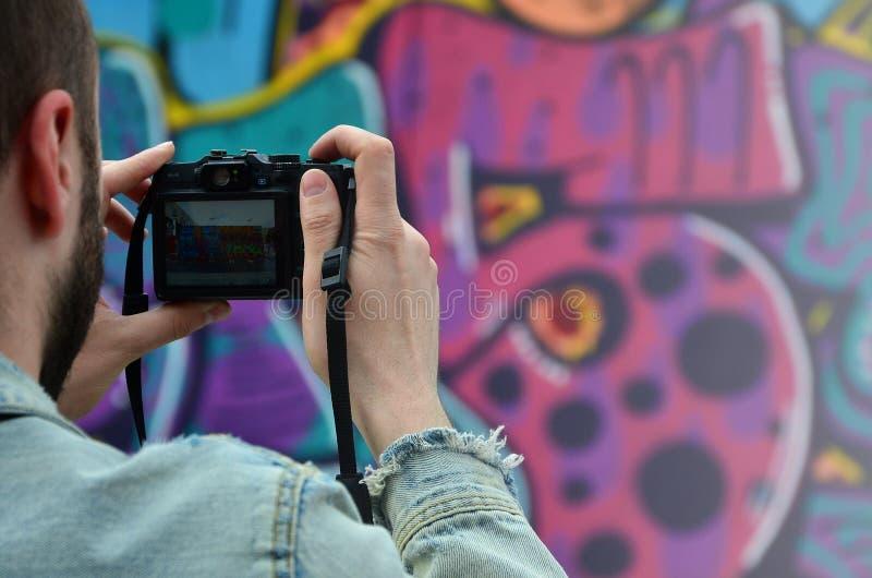 Een jonge graffitikunstenaar fotografeert zijn voltooid beeld op de muur stock foto's