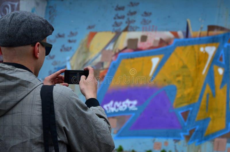 Een jonge graffitikunstenaar fotografeert zijn voltooid beeld op de muur royalty-vrije stock foto