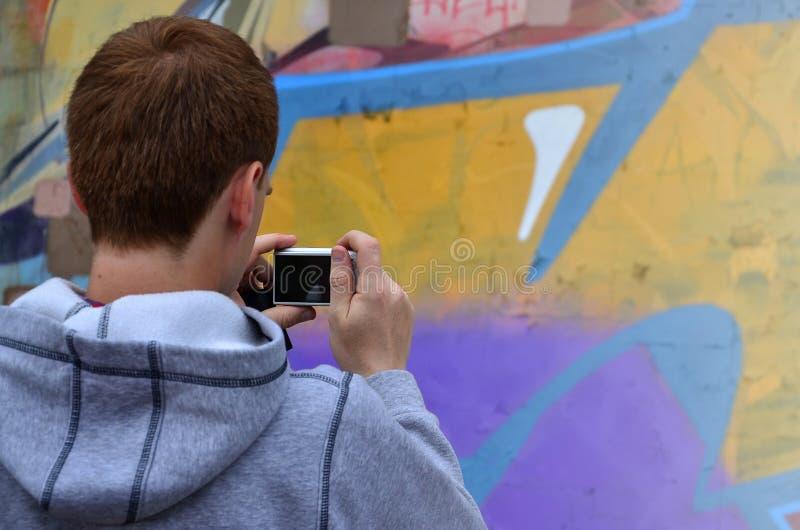Een jonge graffitikunstenaar fotografeert zijn voltooid beeld op de muur royalty-vrije stock afbeelding
