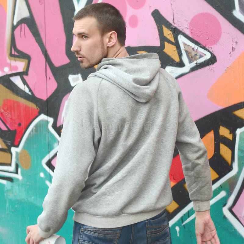 Een jonge graffitikunstenaar kijkt rond terwijl het trekken De vandaal probeert royalty-vrije stock foto