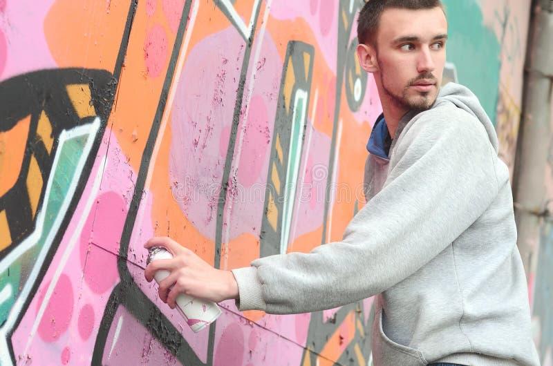 Een jonge graffitikunstenaar kijkt rond terwijl het trekken De vandaal probeert stock foto's