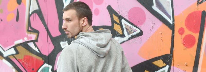 Een jonge graffitikunstenaar kijkt rond terwijl het trekken De vandaal probeert royalty-vrije stock fotografie