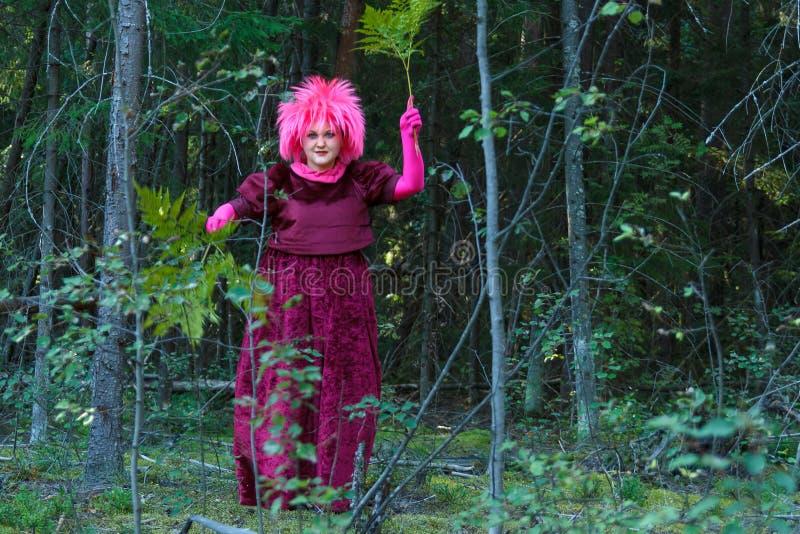 Een jonge heks in paars kleren voert een magisch ritueel uit met een fern in het bos royalty-vrije stock fotografie