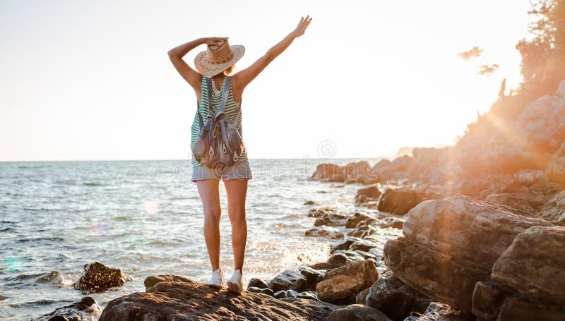 Een jonge hipstervrouw in een hoed en een rokzak met haar handen omhoog, die bovenop een klif staat en de zee ziet bij zonsonderga stock foto's