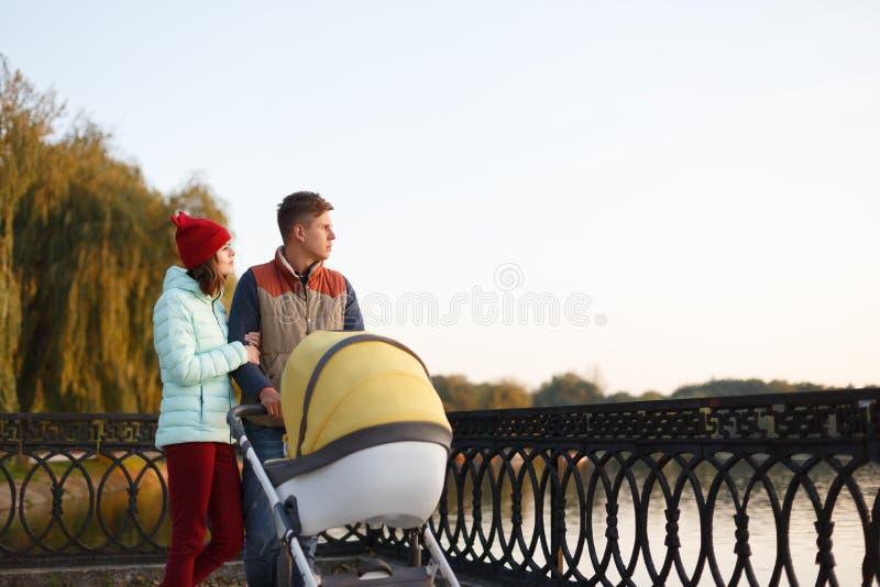 Een jonge houdende van familie loopt door het meer met een wandelwagen Glimlachend ouderspaar met babykinderwagen in de herfstpar stock afbeelding