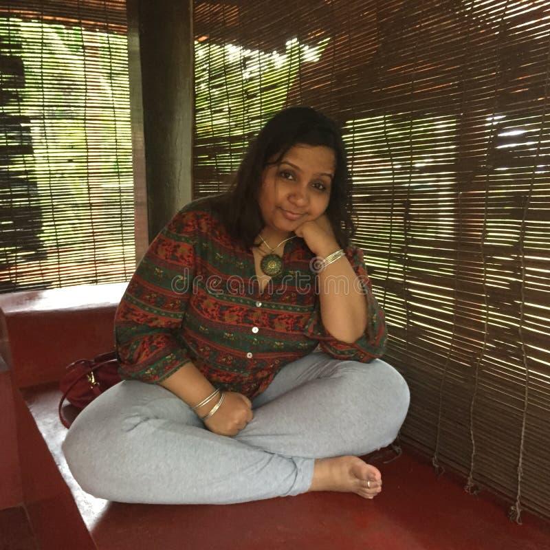 Een jonge Indische dame met gekruiste benen op een portiek stock afbeelding