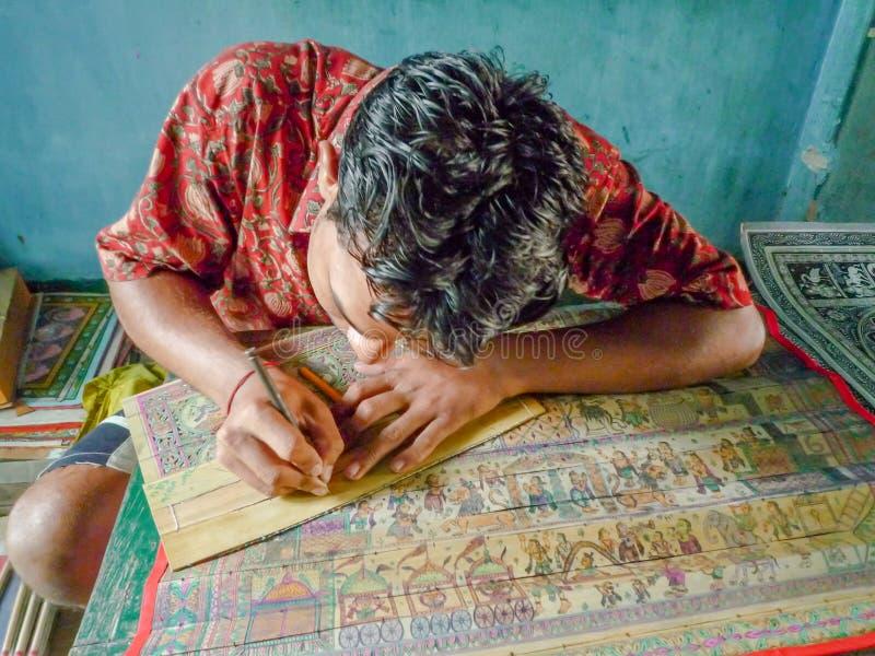 Een jonge Indische mens die voor verkoop bij een platteland van India schilderen royalty-vrije stock afbeelding