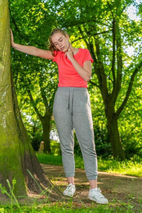 Een jonge jogger leunt tegen een boom en meet haar impuls met haar hand royalty-vrije stock foto