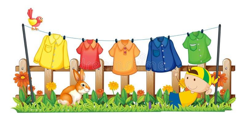 Een jonge jongen die in de tuin dichtbij de hangende kleren spelen royalty-vrije illustratie