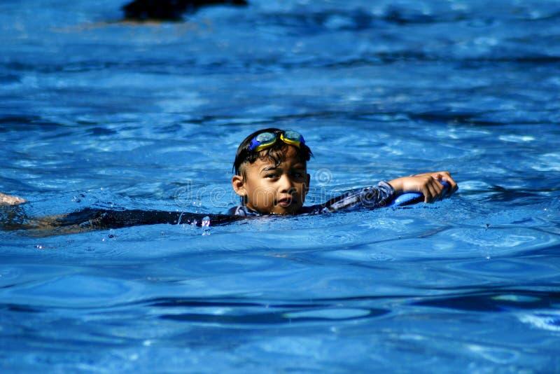 Een jonge jongen zwemt in een zwembad stock foto's