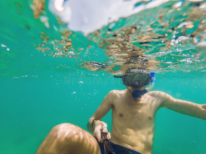 Een jonge Kaukasische het snorkelen mens onder water selfie Thailand stock fotografie