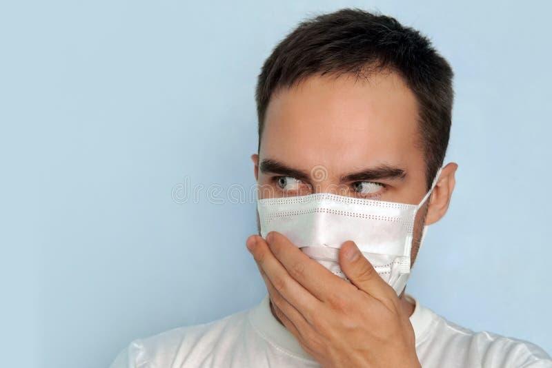 Een jonge kerel behandelt zijn neus in een masker stock afbeeldingen