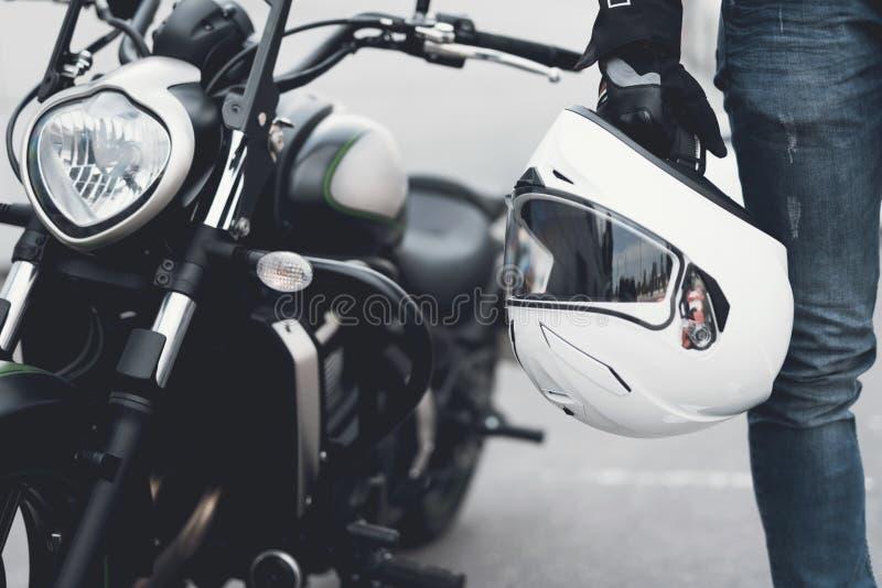 Een jonge kerel bevindt zich dichtbij een elektrische motorfiets stock afbeeldingen