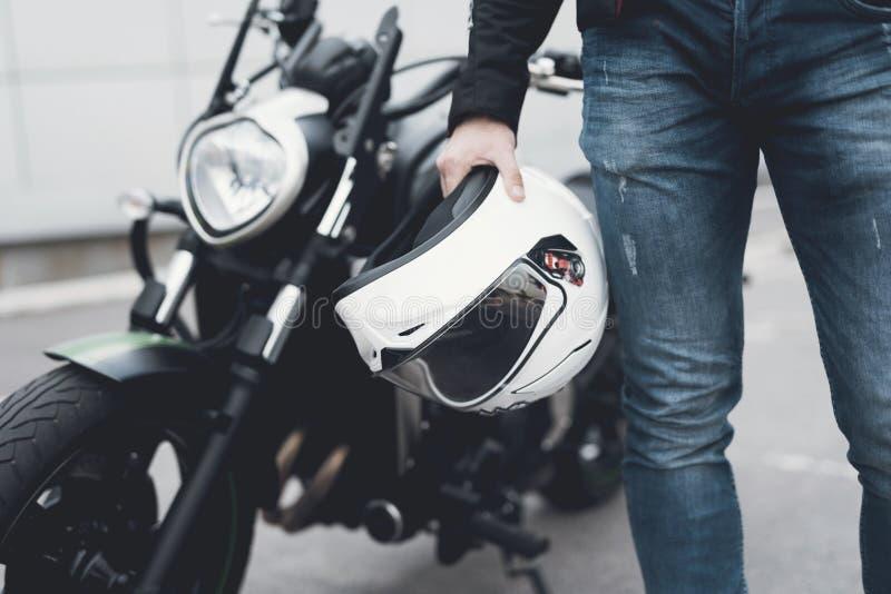 Een jonge kerel bevindt zich dichtbij een elektrische motorfiets royalty-vrije stock afbeelding