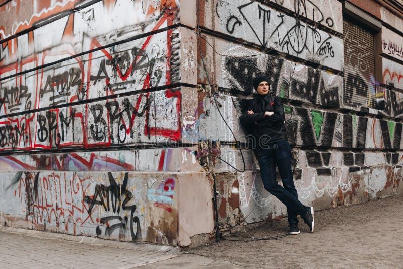 Een jonge kerel bevindt zich naast muur met graffiti royalty-vrije stock fotografie