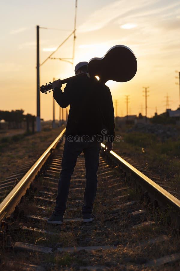 Een jonge kerel bevindt zich op de sporen met een gitaar op zijn schouders bij zonsondergang stock afbeeldingen