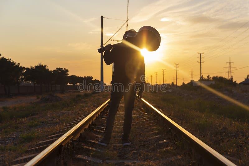 Een jonge kerel bevindt zich op de sporen met een gitaar op zijn schouders bij zonsondergang stock afbeelding