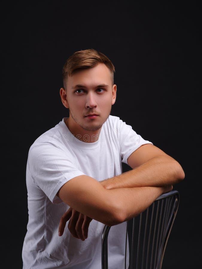 Een jonge kerel die, die op een stoel zitten en de afstand onderzoeken Op een zwarte achtergrond stock afbeeldingen