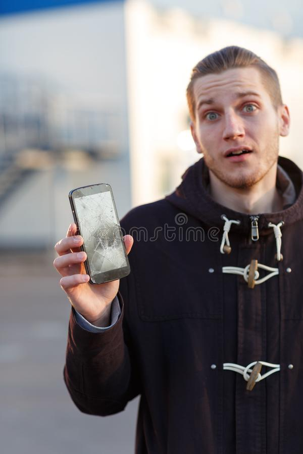 Een jonge kerel die zich op de straat bevinden houdt een gebroken smartphone en is verbolgen royalty-vrije stock foto