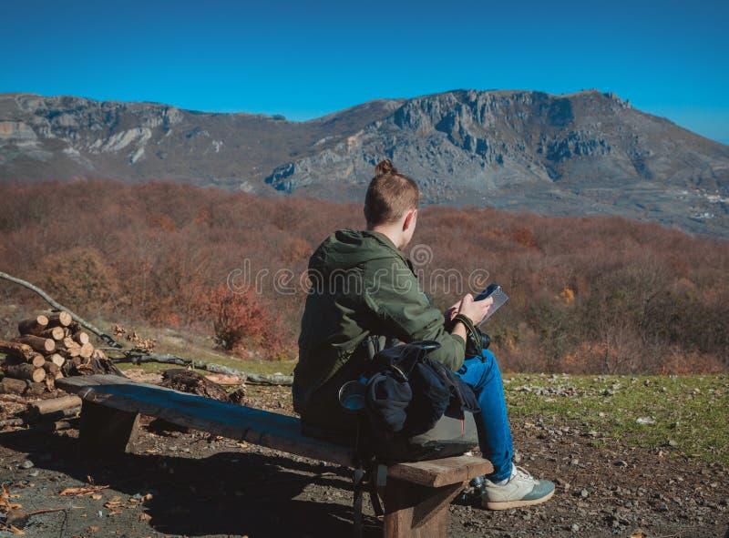 Een jonge kerel gekleed voor wandeling zit hoog in de bergen en kijkt een mobiele telefoon in handen royalty-vrije stock fotografie