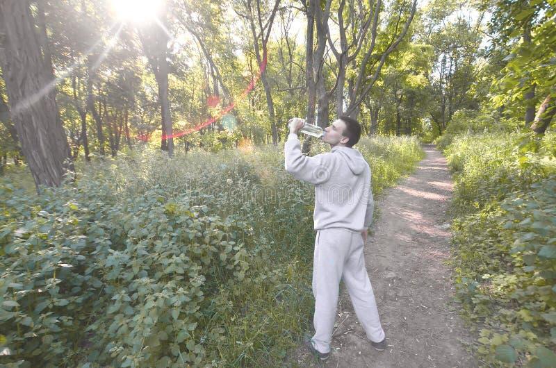 Een jonge kerel in een grijs sportenkostuum drinkt water van een fles amo royalty-vrije stock afbeeldingen