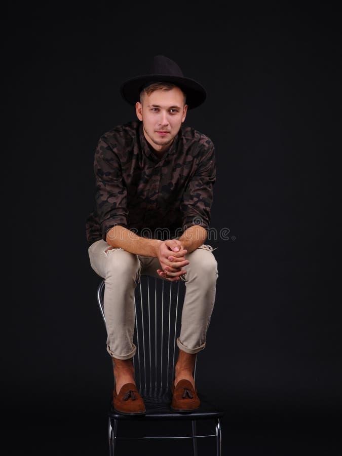 Een jonge kerel in een hoed zit op de rug van de stoel en glimlacht royalty-vrije stock foto's