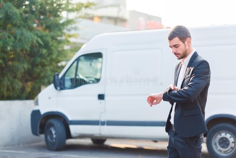 Een jonge kerel in een kostuum bekijkt de tijd op de achtergrond van de auto stock foto