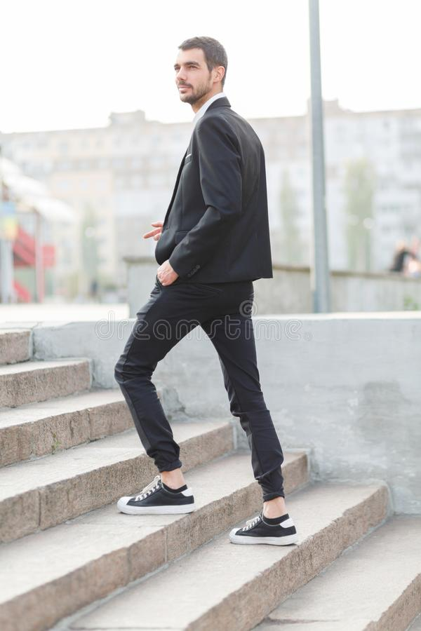 Een jonge kerel met een baard en in een kostuum neemt op de treden in de straat toe buiten royalty-vrije stock fotografie