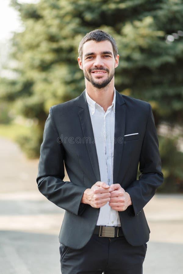 Een jonge kerel met een baard in een kostuum bevindt zich en glimlacht op de straat royalty-vrije stock fotografie