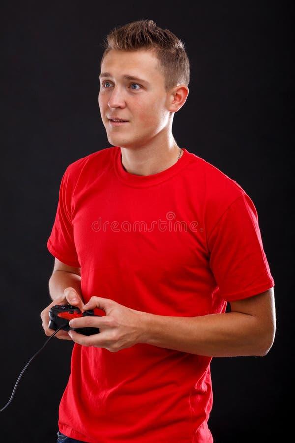 Een jonge kerel met rentespelen in de console die een spelbedieningshendel houden Op een zwarte achtergrond royalty-vrije stock fotografie