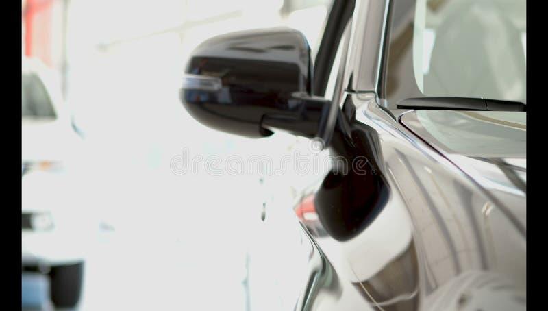 Een jonge kerel onderzoekt vastbesloten een nieuwe auto in het autohandel drijven royalty-vrije stock afbeeldingen