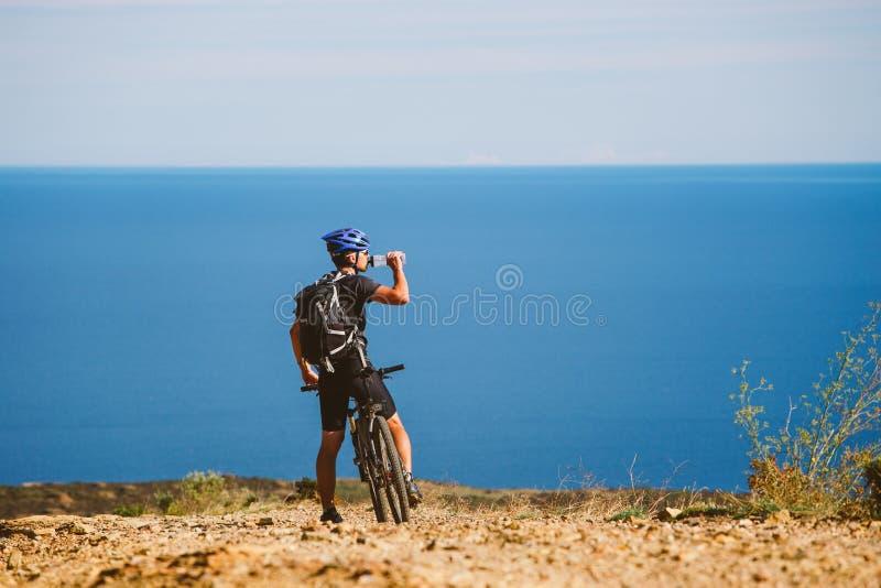 Een jonge kerel op een bergfiets hield op om water van een kruik op een steenachtige weg dichtbij de Middellandse Zee in Spanje t royalty-vrije stock foto's