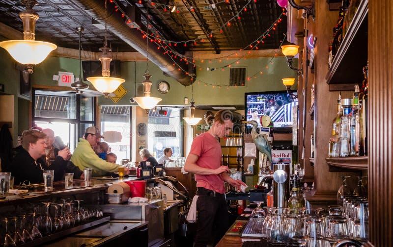 Een jonge kerel werkt in een bar