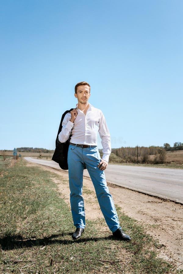 Een jonge kerel in een wit overhemd en blauwe broeken, die zijn jasje over zijn schouder werpen, stock fotografie