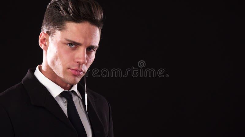 Een jonge kerel zet op één oortelefoon en kijkt als een ernstige lijfwacht stock foto