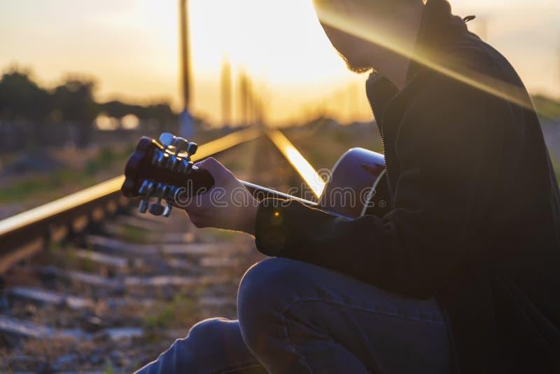 Een jonge kerel zit op de sporen en speelt de gitaar royalty-vrije stock foto's