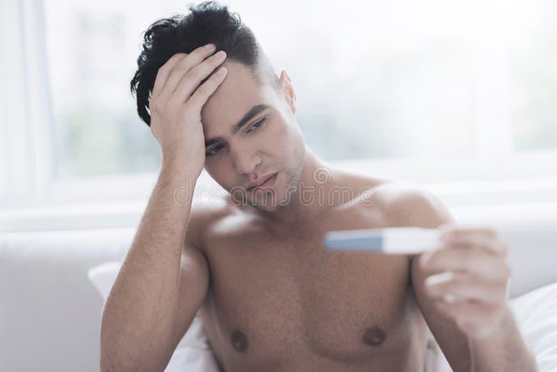 Een jonge kerel zit op het bed en houdt een test voor zijn meisjes` s zwangerschap royalty-vrije stock fotografie