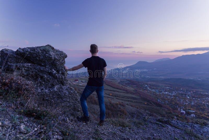Een jonge kerel in een zwarte T-shirt bevindt zich bovenop een berg, met van hem terug naar de camera en de starende blikken suns royalty-vrije stock afbeelding