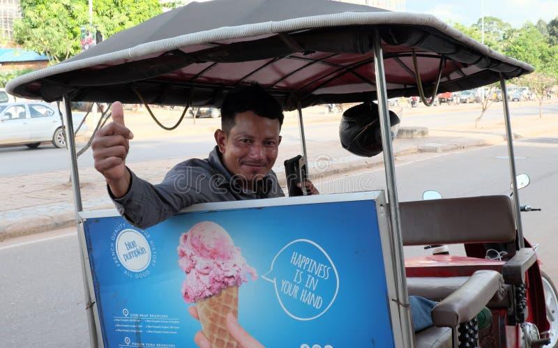 Een jonge Khmer taxibestuurder nodigt toeristen uit om uit zijn diensten voordeel te halen De bestuurder royalty-vrije stock foto's