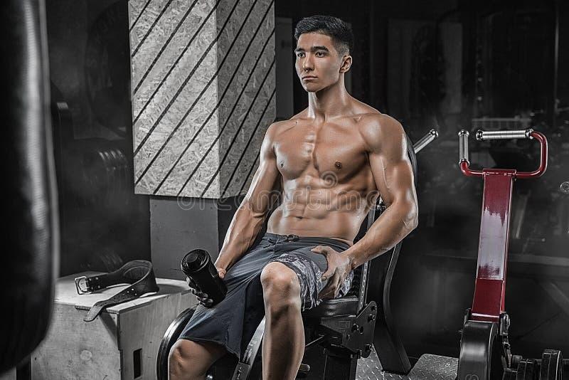 Een jonge knappe Aziatische bodybuilder, die na een machtscircui rusten royalty-vrije stock foto's