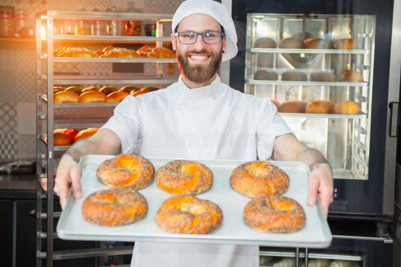 Een jonge knappe bakker die verse ongezuurde broodjes met papaverzaden houden op een dienblad op de achtergrond van een oven en e stock afbeelding