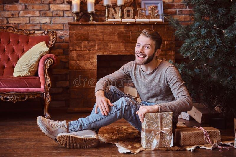 Een jonge knappe een camera bekijken en mens die terwijl het zitten op die een vloer glimlachen door giften wordt omringd royalty-vrije stock afbeelding