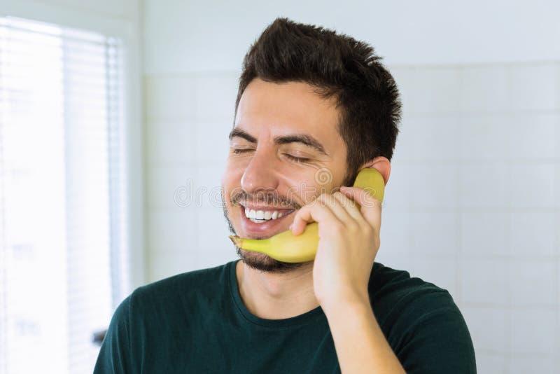 Een jonge knappe donkerbruine mens spreekt op de telefoon, in plaats van het gebruiken van een banaan royalty-vrije stock afbeelding