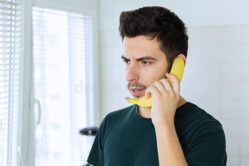 Een jonge knappe donkerbruine mens spreekt op de telefoon, in plaats van het gebruiken van een banaan stock afbeeldingen