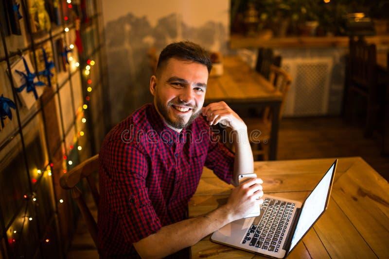 Een jonge knappe Kaukasische mens met baard en toothy glimlach in rood geruit overhemd werkt achter laptop zitting bij houten lij stock fotografie
