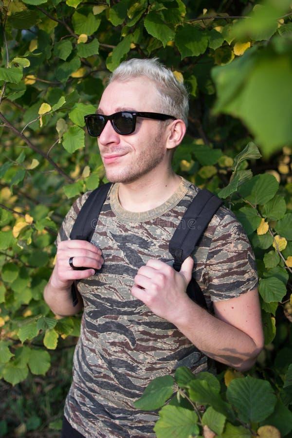 Een jonge knappe mens die t-shirt en zwarte zonnebril op achtergrond van groene en gele bladeren dragen stock afbeeldingen