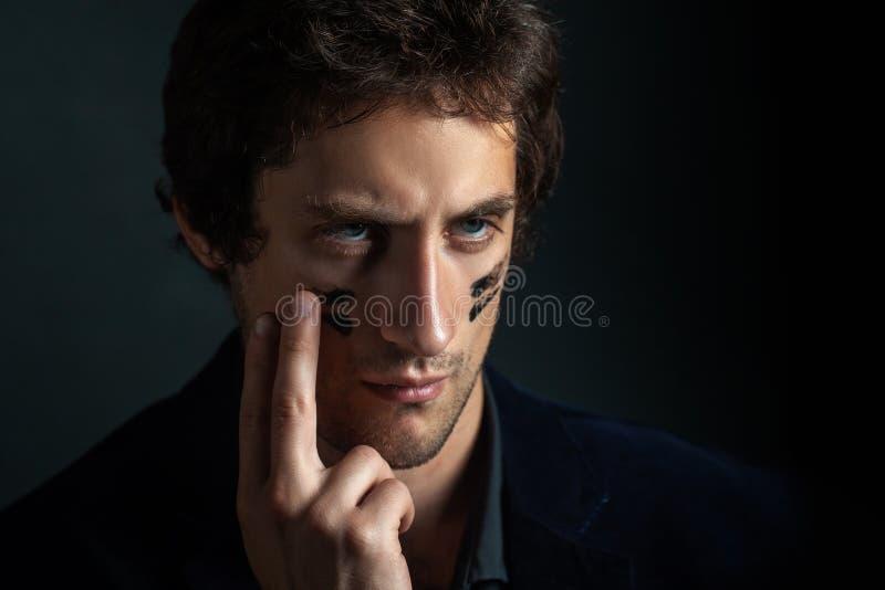 Een jonge knappe mens met een lichte ongeschoren gezicht en een onbetwistbaarheid in zijn ogen, zet een zwarte oorlogsverf op zij royalty-vrije stock fotografie